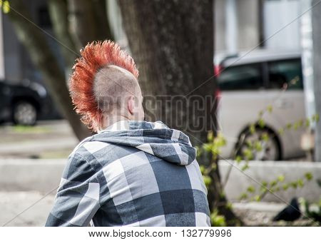 The young guy the punk with an original red hairdress.