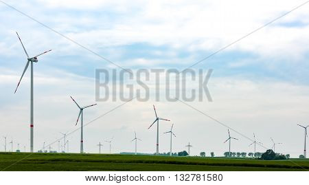 Panorama of the field with eco electric windmills.Windmills outdoor under blue sky on green field.Group of eco windmills for renewable electric energy production.