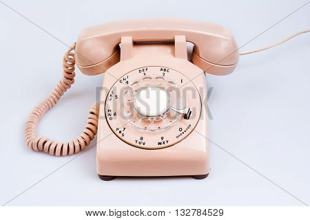 Old cream colored rotary style telephone on white