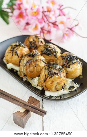 Close up of takoyaki on wooden table with chopsticks Japanese food