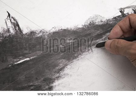A hand holding charcoal doing charcoal painting