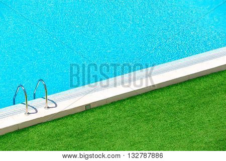Infinity pool on the bright summer day with green grass around.Swimming pool with stairs into the water.Hotel swimming pool with sunny reflections close up view.
