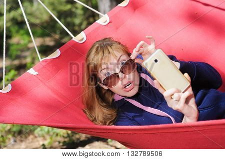 Shocked girl staring at camera In Hammock. Young woman in glasses on red hammock taking pictures with cell phone smartphone. Redhead woman with freckles. Forest mountains in background.