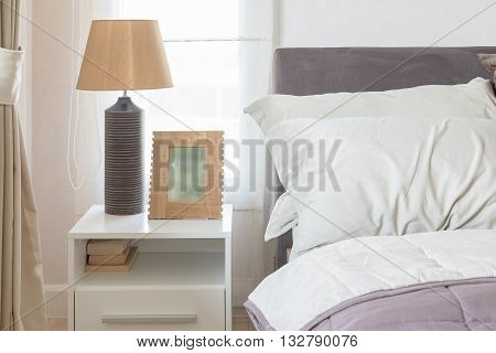 White Pillow On Bed With Picture Frame And Lamp