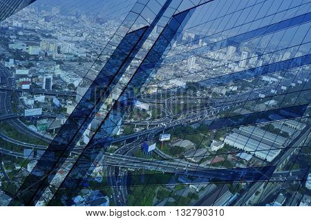 Reflect of aerial view of cityscape expressway and highway on window glass tower blue tone Bangkok Thailand