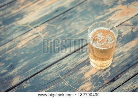 Beer in glass with ice and froth on a wood table process in vintage style