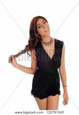A pretty young woman in a black jump suit playing with her hair isolated for white background.