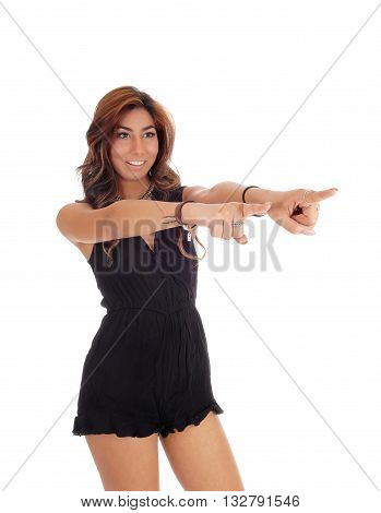 A pretty young woman in black shorts standing in profile pointing with both fingers at you isolated for white background.