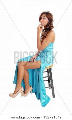A gorgeous young woman sitting in a blue evening or broom dress showing her long legs isolated for white background.