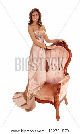 A lovely young woman in a gold color evening dress standing on a pink armchair isolated for white background.