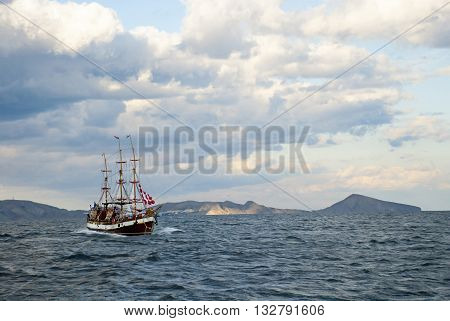 Sailing ship among the islands in the troubled sea
