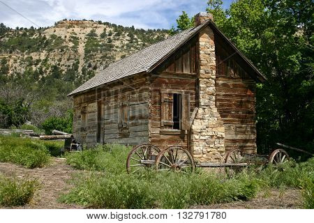 a wagon frame parked beside an old log cabin in Utah