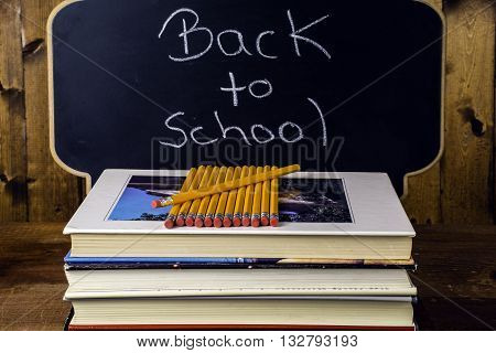 stack of books and pencils on wood background in front of chalkboard written back to school