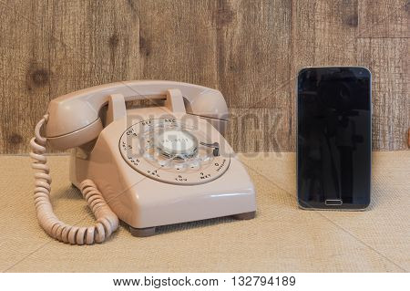 Vintage Rotary telephone next to a modern cell phone