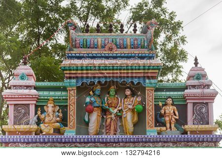 Chettinad India - October 17 2013: Entrance to the shrine of Shani known as Satan in the West in Kadiapatti. Image features wedding of Shiva and Parvati. The blue skinned person is Lord Vishnu giving his sister the green-skinned female in the middle Devi