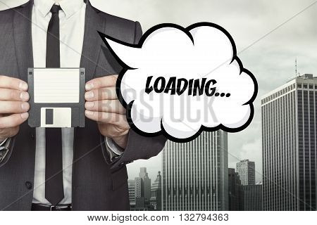 Loading text on speech bubble with businessman holding diskette on cityscape background