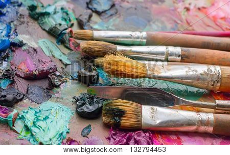 Used Brushes On An Artist's Palette Of Colorful Oil Paint For Drawing