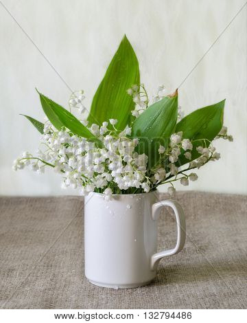 Bouquet of white lily-of-the-valley on the simple rustical background.