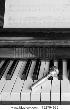 A trumpet mouthpiece upon the piano keys close up