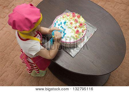 Little girl children decorate cream cake on table