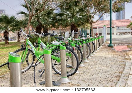 Tel Aviv-Yafo, Israel - January 21, 2016:  Light green city bikes for rent parking in south Tel Aviv area. There are some green short palms