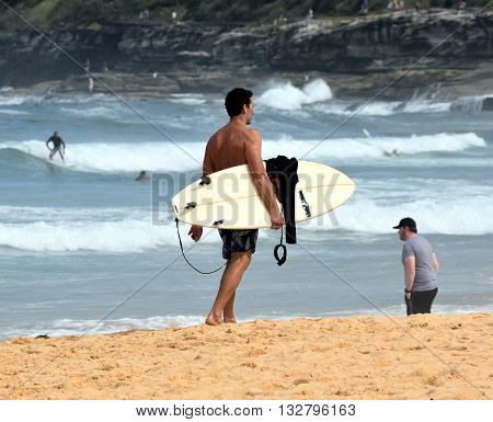 Amateur surfer is walking on the beach with his surfboard