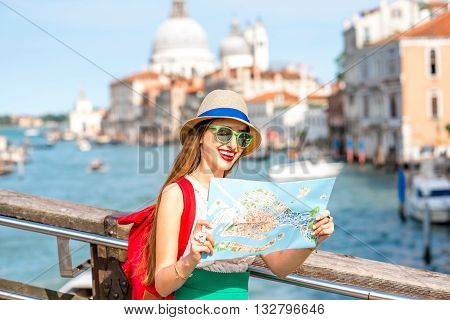Young female traveler with hat and backpack traveling with paper map on the bridge with great view on Grand canal in Venice.