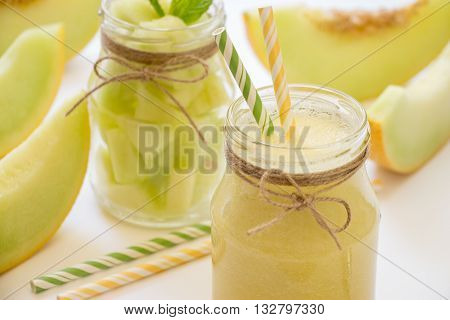 In front a jar with melon smoothie diagonally behind a jar with melon pieces near cut slices of melon straws on a white background. Melon smoothie and salad in 2 jars. Horizontal. Daylight. Close-up.
