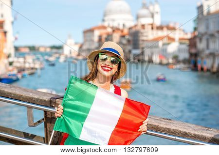 Young female traveler with italian flag on the bridge with geat view on Grand canal in Venice