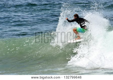 Amateur surfer is surfing on the beach