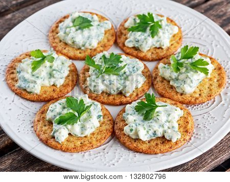 Biscuit cracker appetizers with cottage cheese and parsley topping.