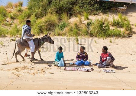 NILE, EGYPT - FEBRUARY 8, 2016: Kids selling traditional crafts on the banks of the Nile.