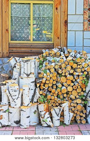 Birch firewood Stack of firewood freshly sawn birch from the wall of a country house