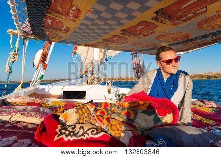 NILE, EGYPT -  FEBRUARY 8, 2016: Tourist enjoying felucca trip on the Nile.