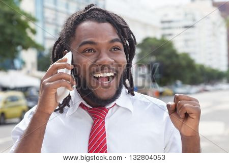 Happy african american businessman with dreadlocks at phone outdoor in the city