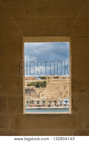 Window in the fortification tower in Gardjola Gardens in the city Senglea island Malta. View on fortification of the capital Valletta. Cloudy sky.