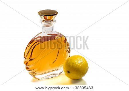 Bottle of brandy and lemon on white background