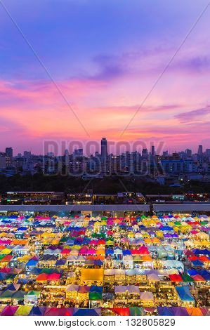 Night Flea market aerial view, with city downtown background, dramatic sky background over