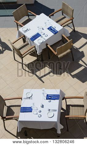 High Angle View Of Setting Tables And Chairs In Sunlight.