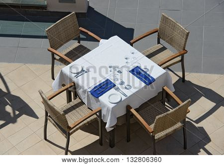 High Angle View Of Setting Table And Chairs In Sunlight.