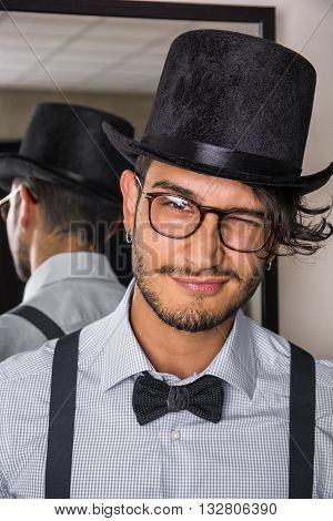 Portrait of brunette young man in glasses, hat, bow-tie, suspenders and shirt looking at camera. Mirror behind him