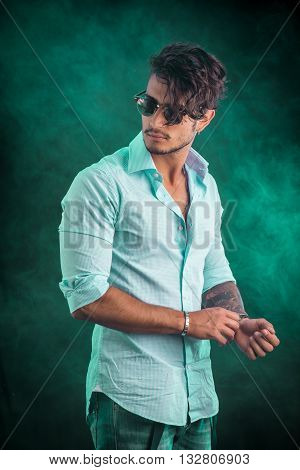Portrait of brunette young man in light blue shirt and jeans, standing in studio shot against dark smoky background