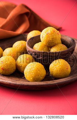 Indian sweet bundi laddu or motichur laddu served in a carved woodel bowl and plate with drapery or table napkin, selective focus