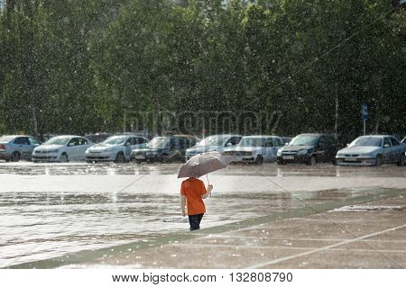 boy with an umbrella standing under the rain in front of the parking lot