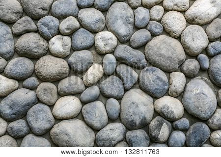 The natural stone of granite breed rounded by a current of water on the cement basis