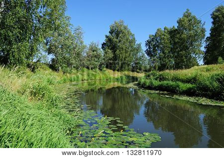 Country landscape with small slow river in summer time