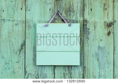 Blank mint green sign hanging on antique rustic shabby wood background