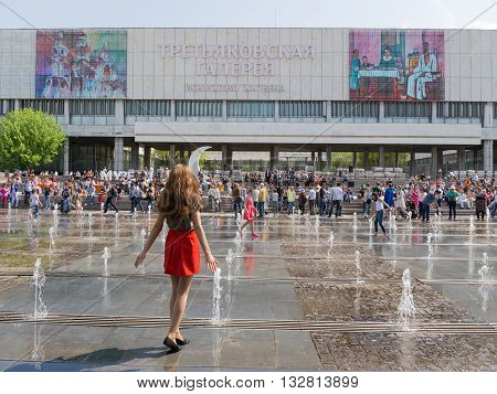 Moscow - May 9 2016: A young girl in a red skirt goes to great music fotanu Muzeon in the park and the orchestra plays the music and a lot of people rest May 9 2016 Moscow Russia
