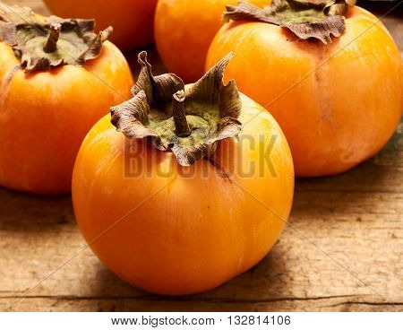 Fresh and sweet persimmons propped up on an old wooden table