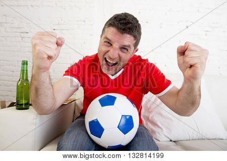 young fan man watching football game on television wearing team jersey celebrating goal happy on sofa couch at home with ball and beer bottle in crazy enthusiastic face expression